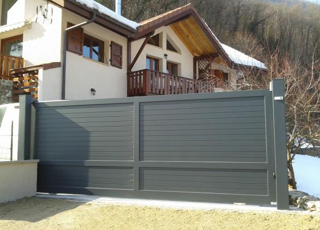 Portail coulissant gris devant maison de montagne