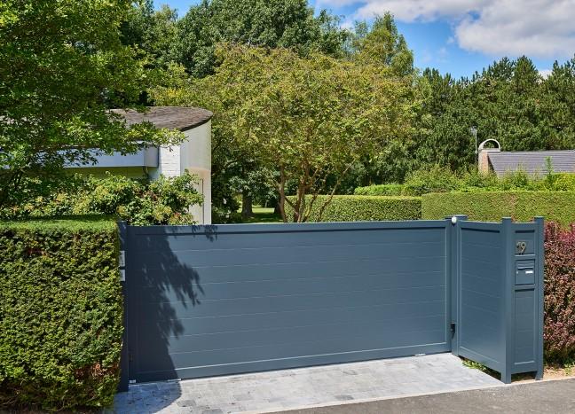 Portail coulissant en aluminium délimitant l'entrée d'une maison